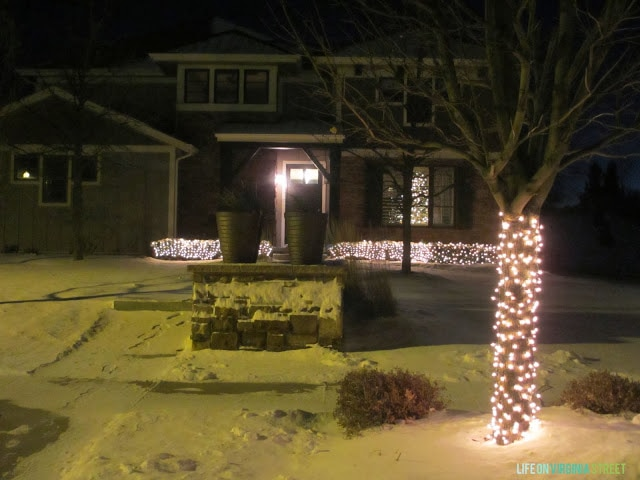 The outside of the house with snow on the ground and trees with lights.