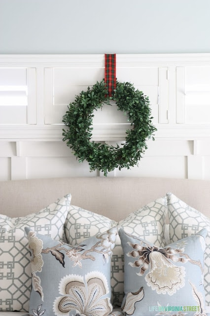 The green wreath with a plaid ribbon above the bed.