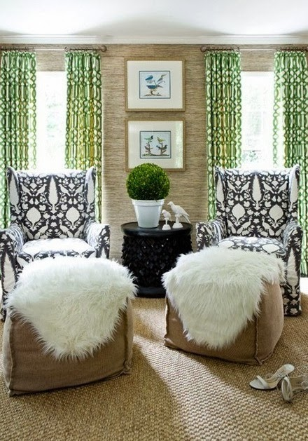 Green curtains, black and white armchairs with faux fur.