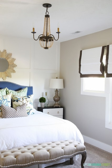 Guest Bedroom with blue headboard, board and batten walls and ribbon-trimmed roman shades
