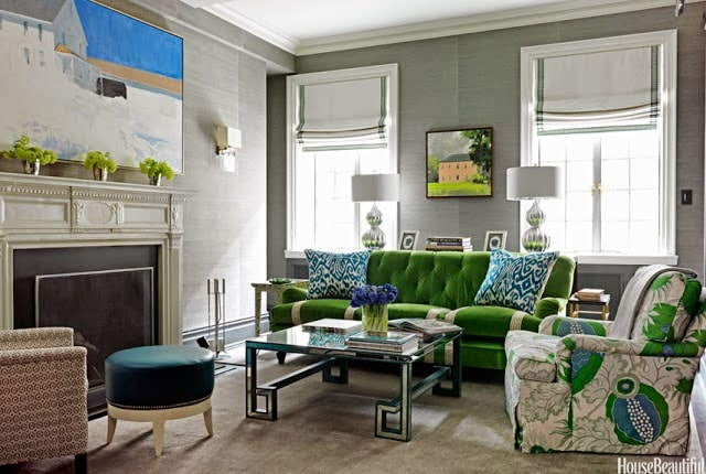 Emerald green couch and floral armchair in living room by the fireplace.