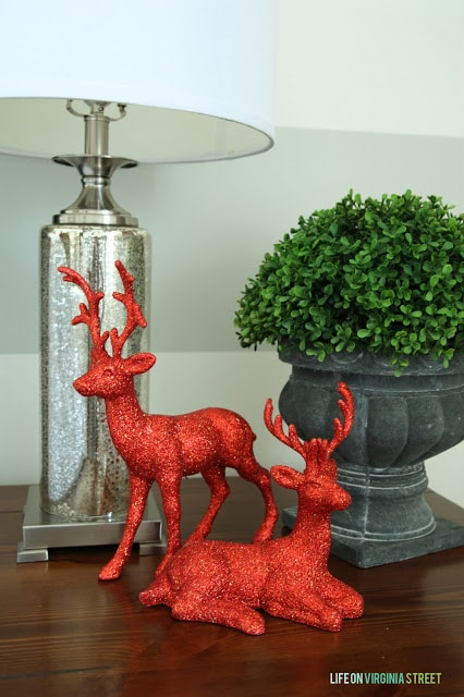 Red sparkly deers are on the night table beside the bed.