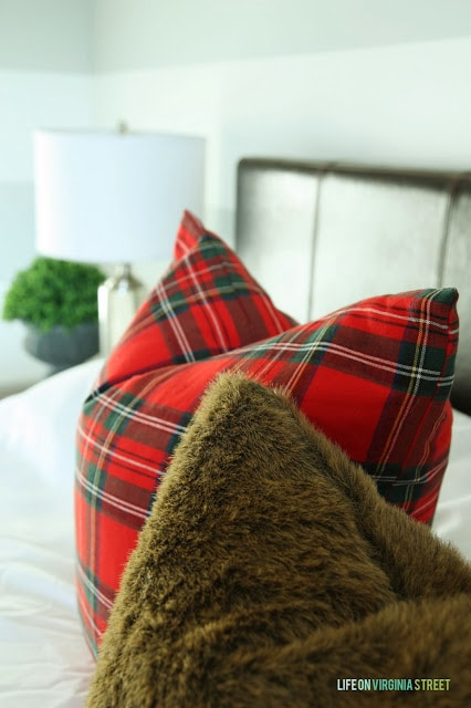 Red plaid and faux fur pillows are on the bed.