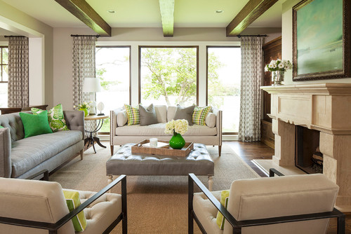 Neutral living room with green pillows and green glass on coffee table.