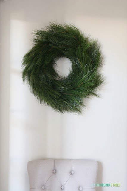 Large green wreath hanging on white wall.