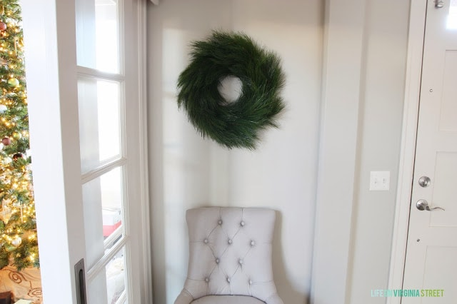Green wreath hanging in room with large window and a chair underneath it.