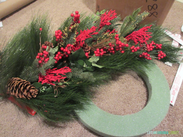 Wreath material with pine cones and red berries.