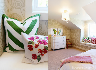 A floral pillow beside the green striped pillow in a window sill in a small bedroom.