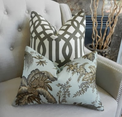Two pillows on a chair one is a nature inspired pillow in brown and light blue.