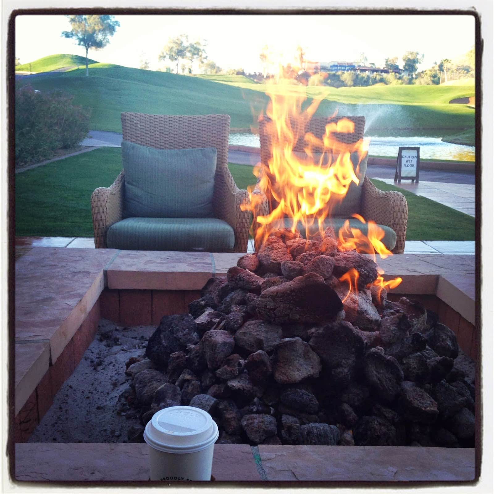 A fire pit with two chairs around it.
