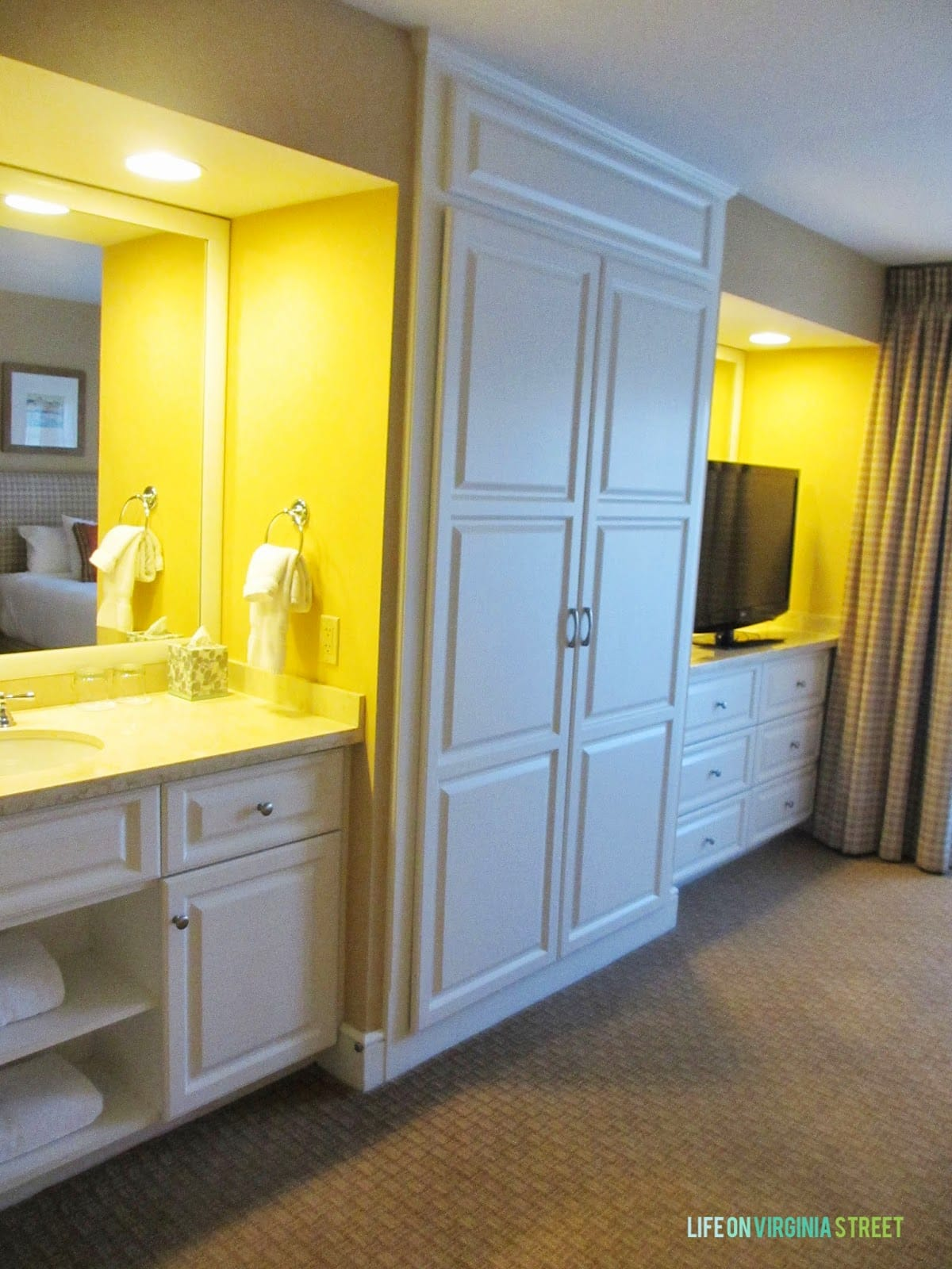 A bedroom vanity and large white closet.