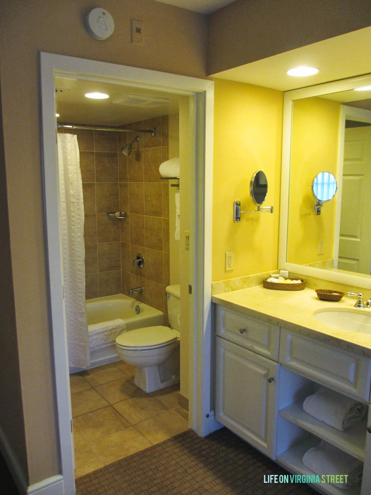 A sink and vanity plus the bathroom with a tub.