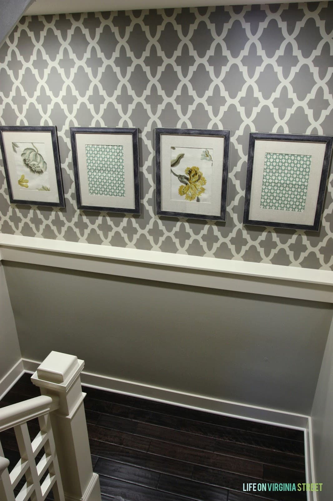 A staircase that has been stencilled with pictures hanging on the wall.