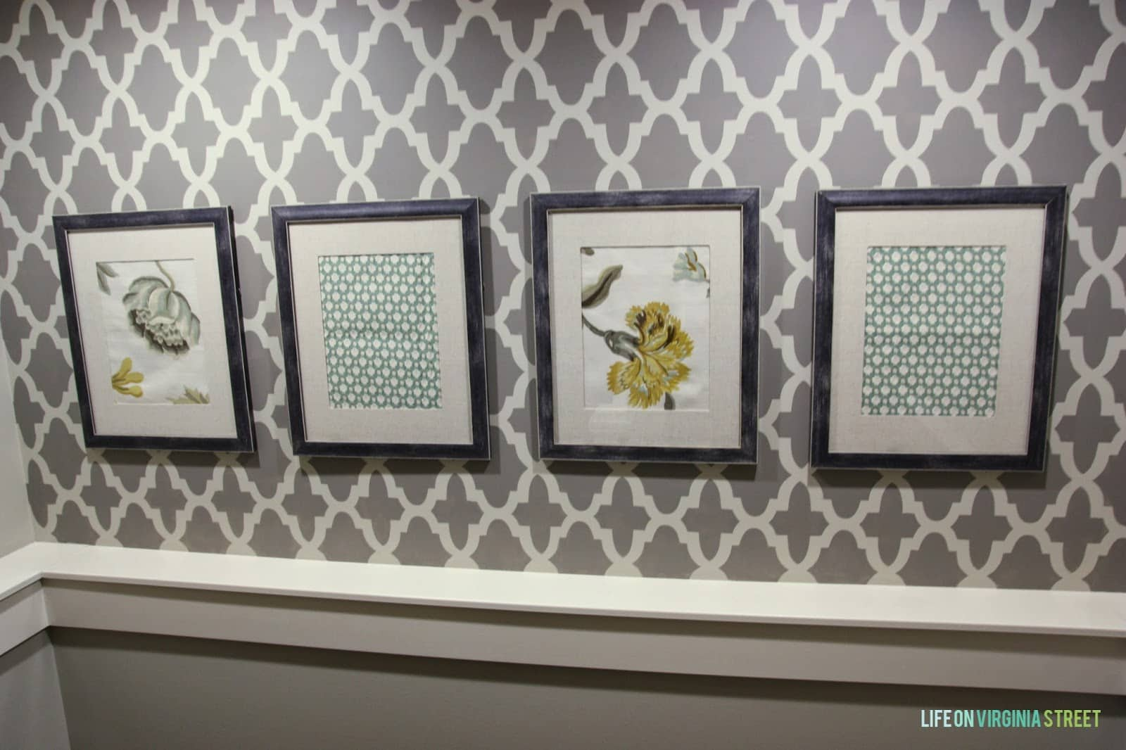 Four pictures on the stencilled wall.