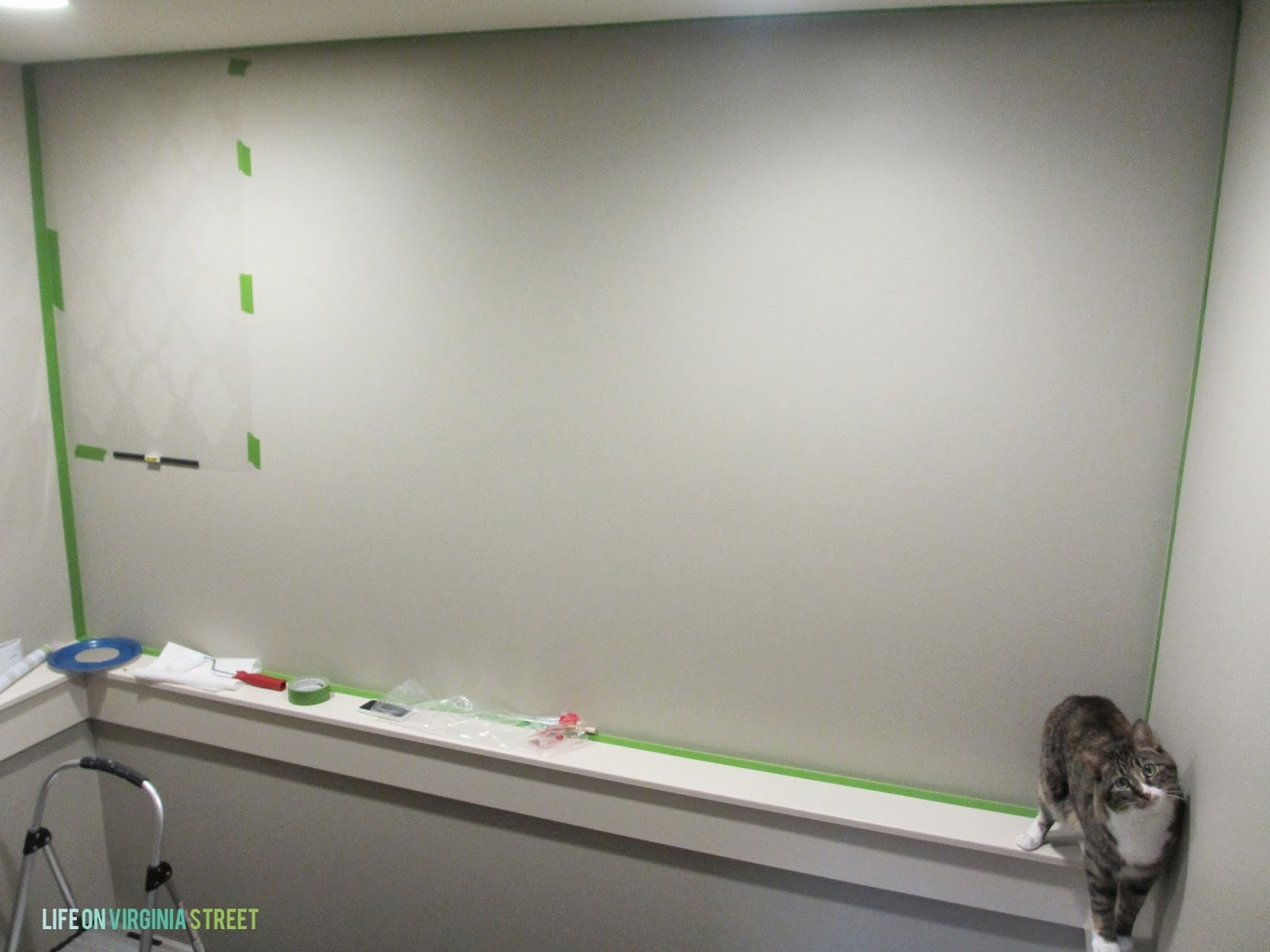Taping the wall for stencilling.  Henley the cat is on the ledge.
