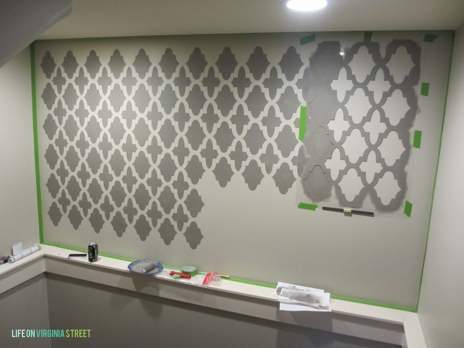 Painting the stencils on the wall in a grey color.