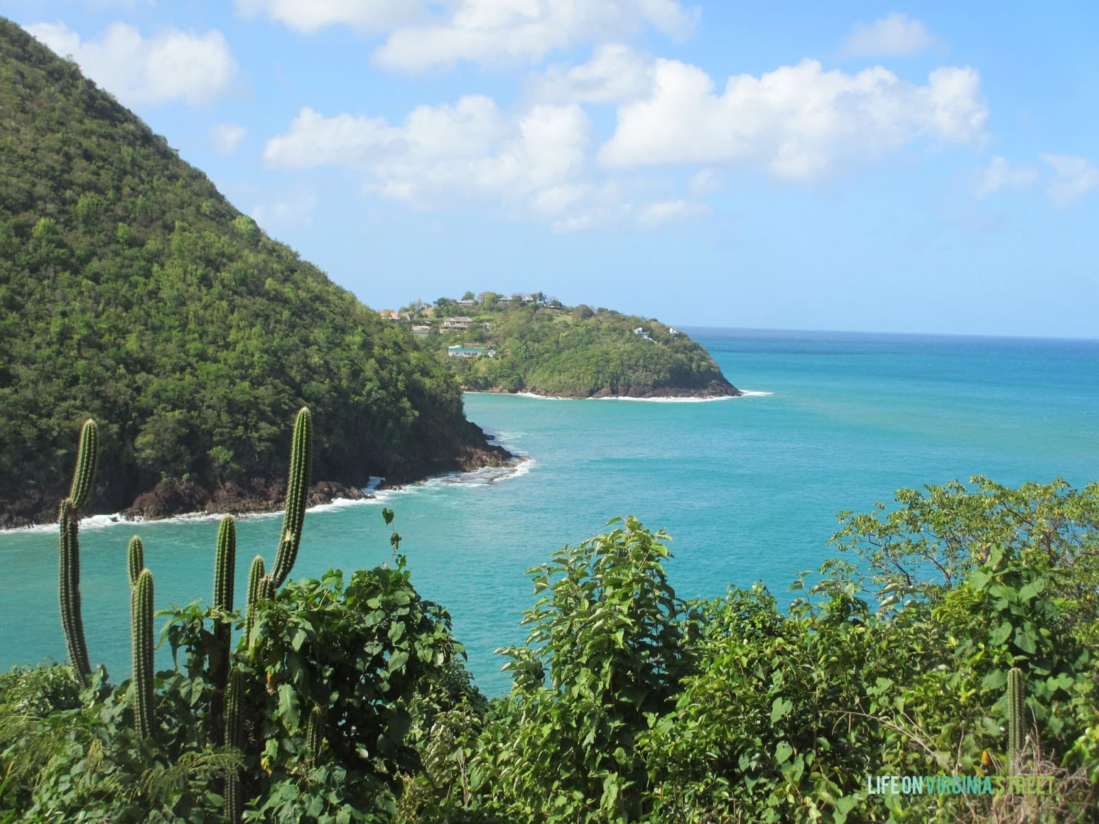 Large hills with turquoise blue water and lush greenery.