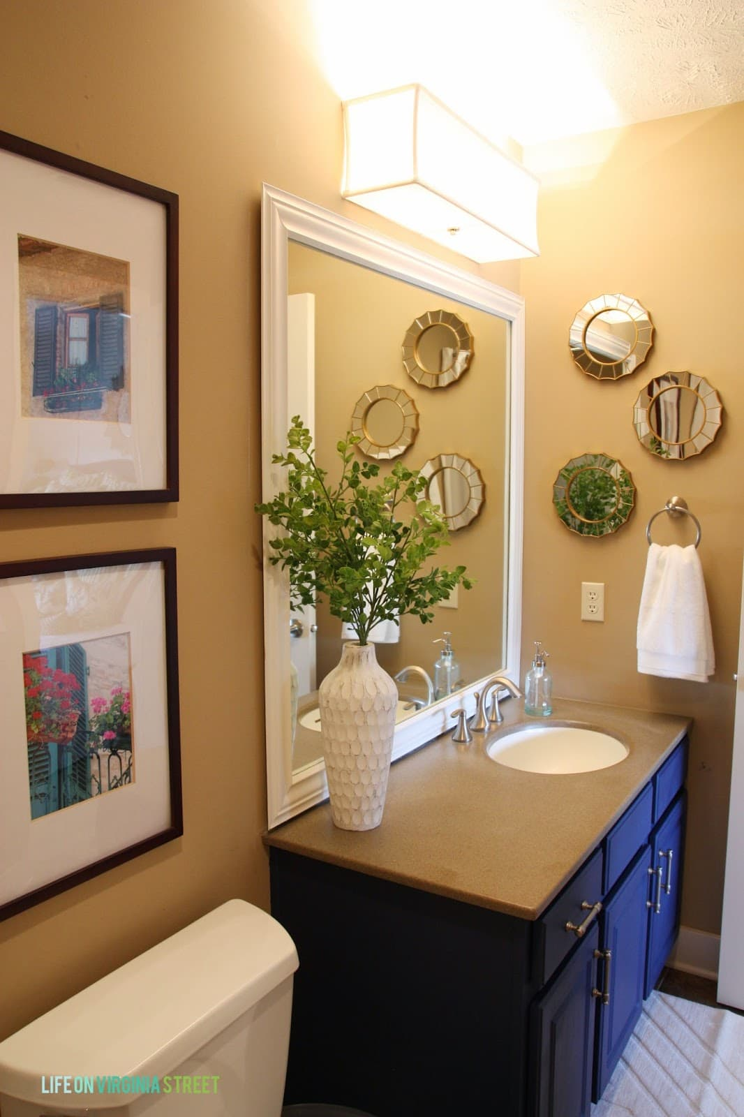 In addition to making over the vanity, I also added a lot more interesting pieces and accessories to the space like these small round mirrors with gold trim and this white vase.