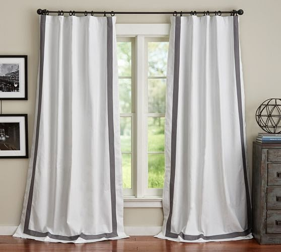 White and grey drapes hanging that just touch the floor.