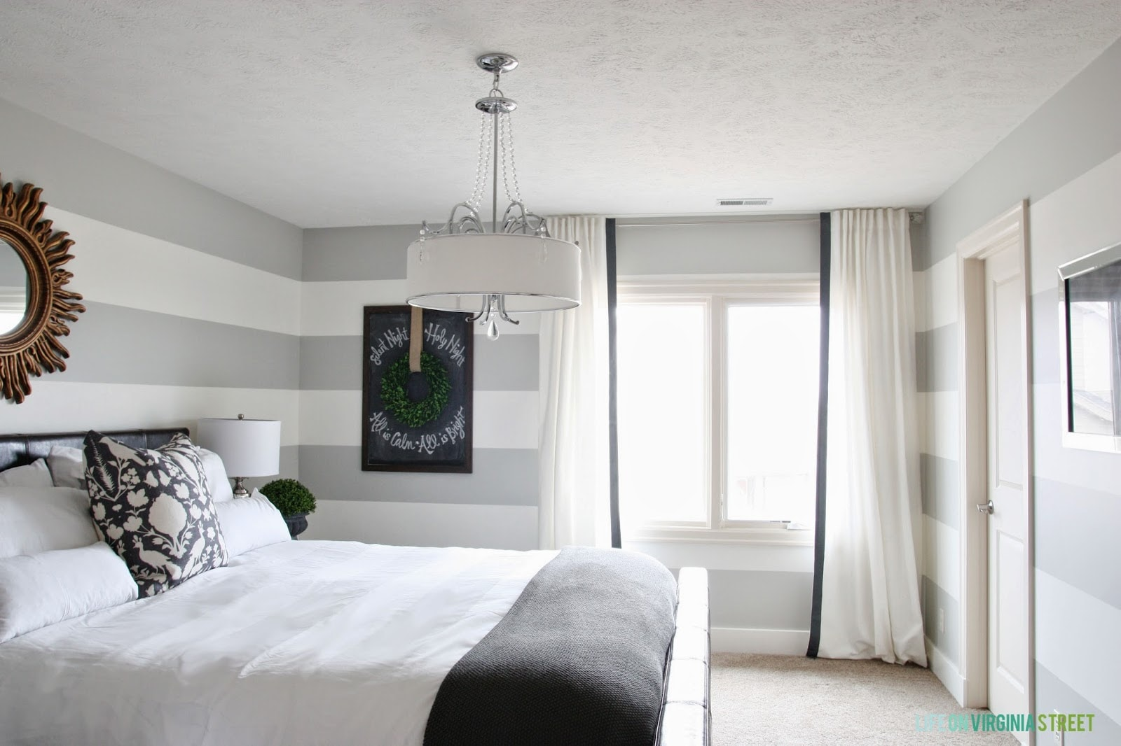 A bright bedroom with the curtains hanging in the window. A large chandelier is above the bed.