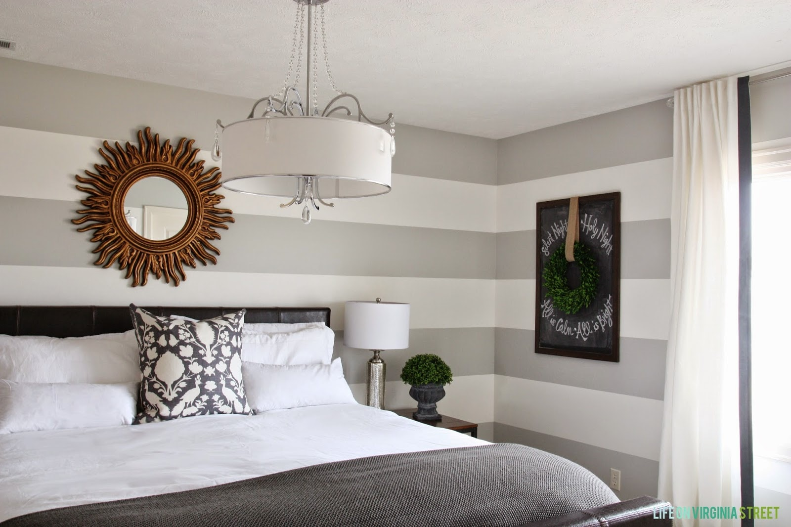 A large gold mirror is behind the bed on the wall in the bedroom.