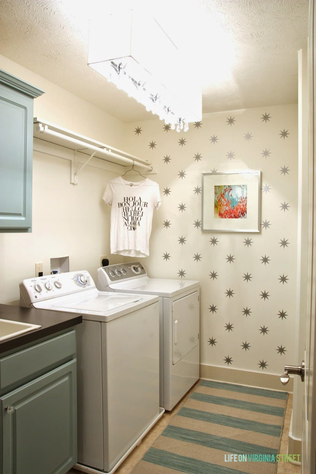 White laundry room with star decals, aqua cabinets, striped rug and colorful art.