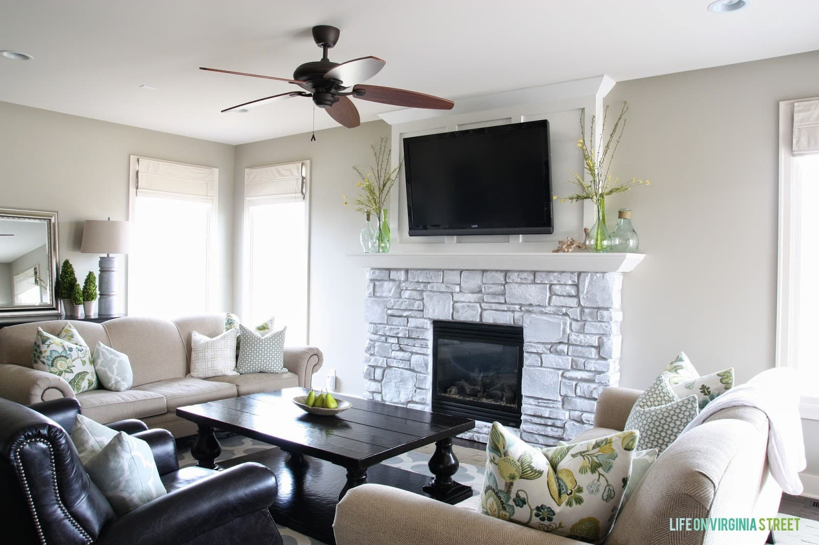 A neutral living room with a whitewashed stone fireplace!