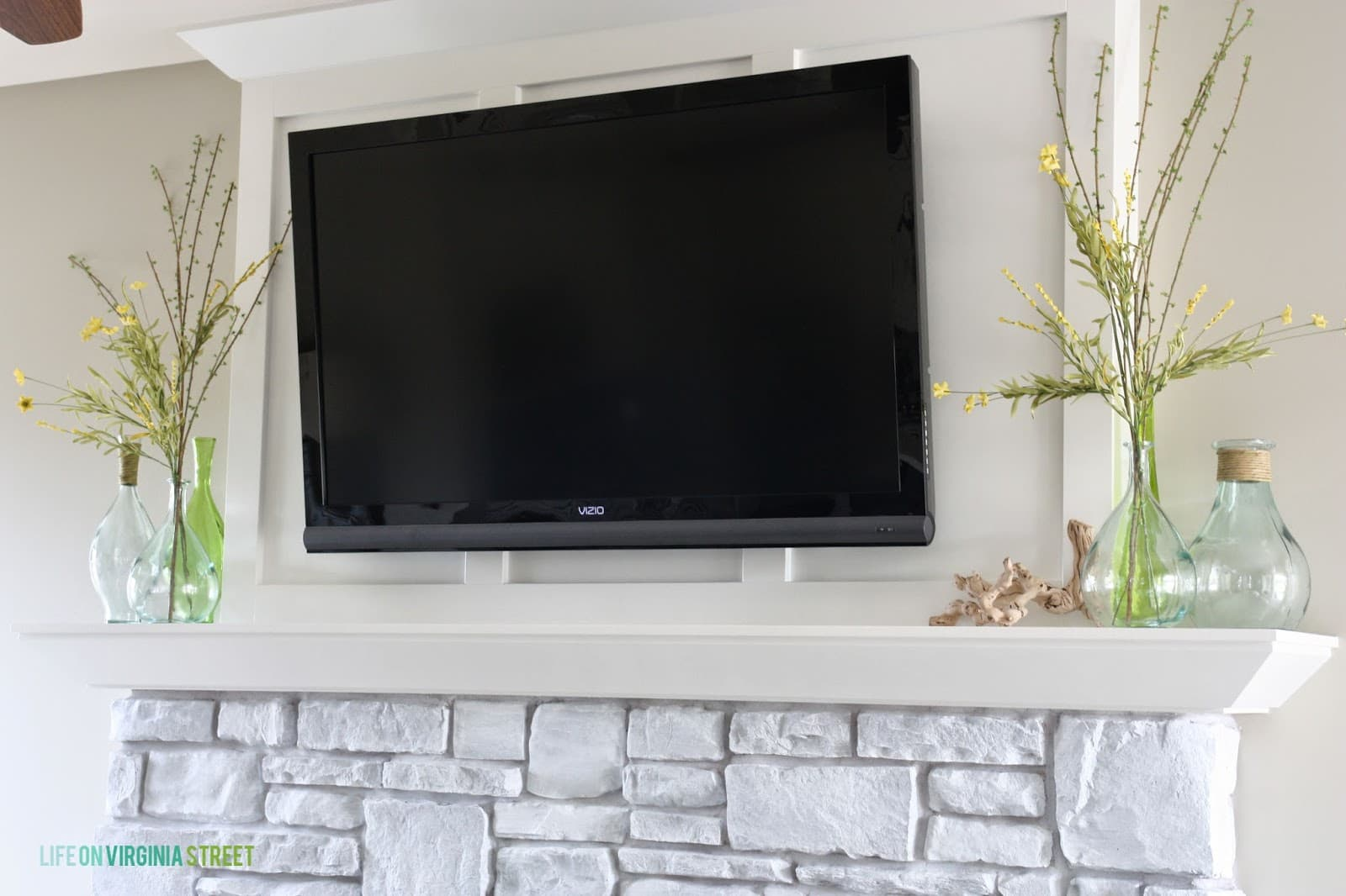 The final look- TV mounted above the updated whitewashed fireplace stone.