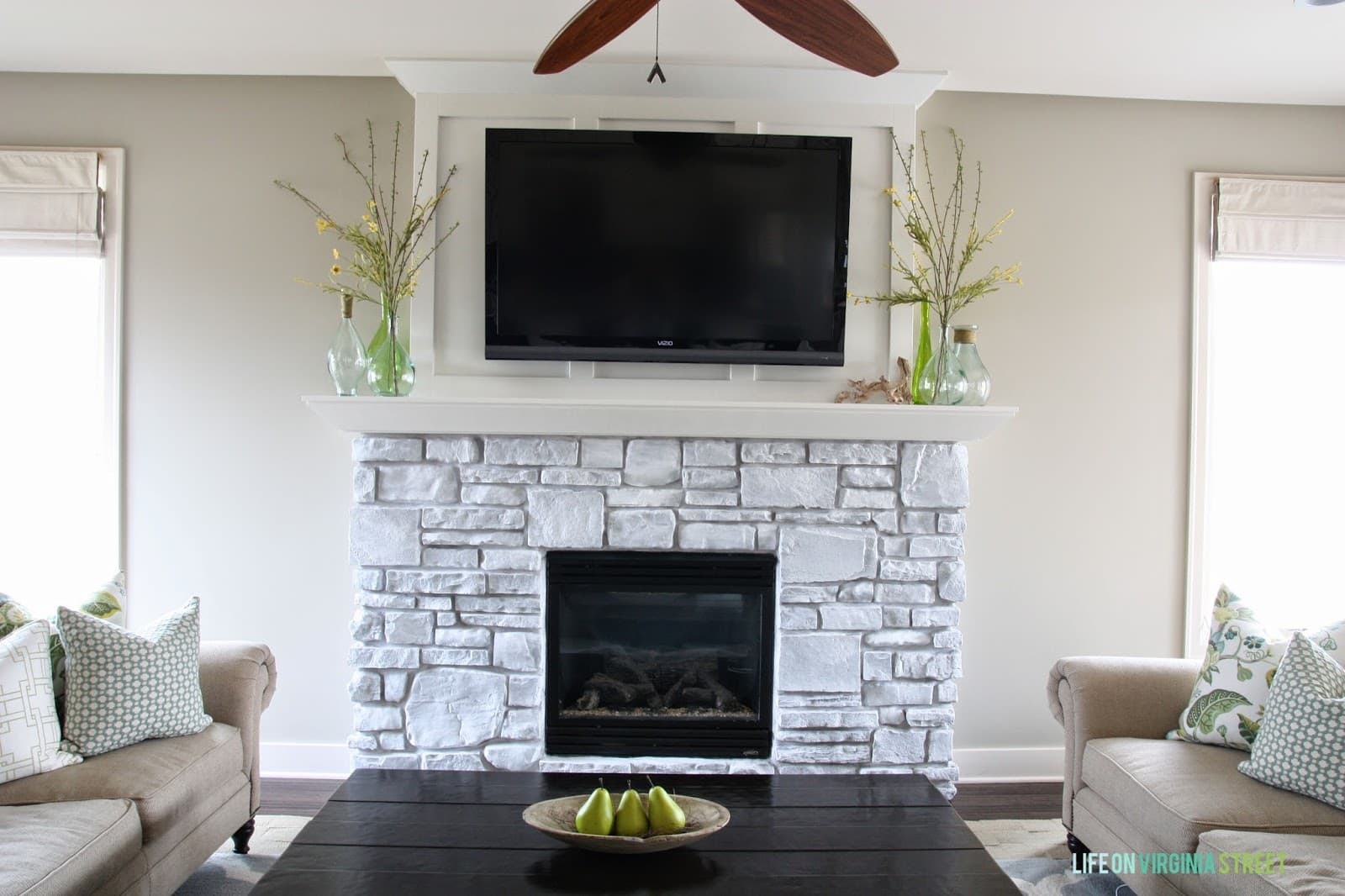 A whitewashed stone fireplace with board and batten feature wall.