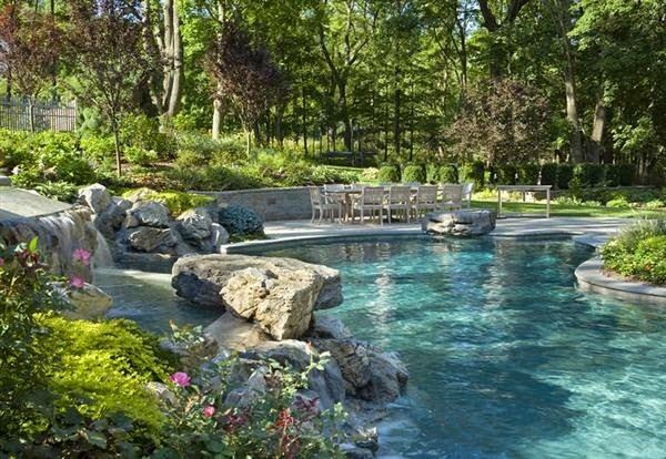 This pool landscaping is similar to what I would like to see. Rugged, with a waterfall feature.