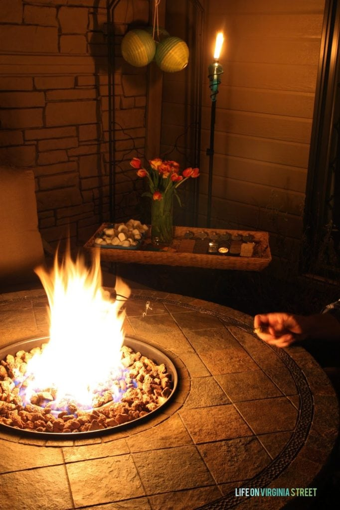 A outdoor patio fire pit that is lit and a marshmallow being heated up.