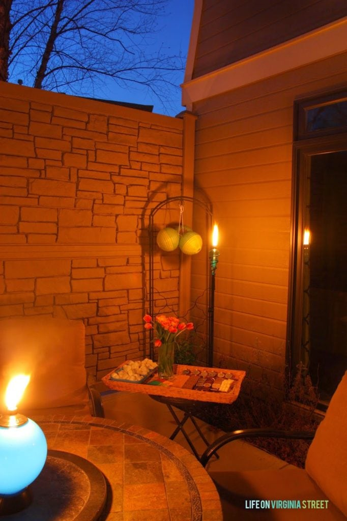A dark night sky with a patio latern that is lighting up the patio.