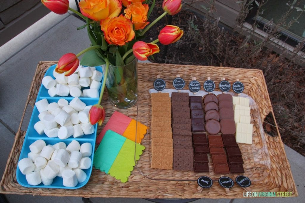 An up close look of the wicker basket with a vase filled with flowers and goodies to make s'mores.