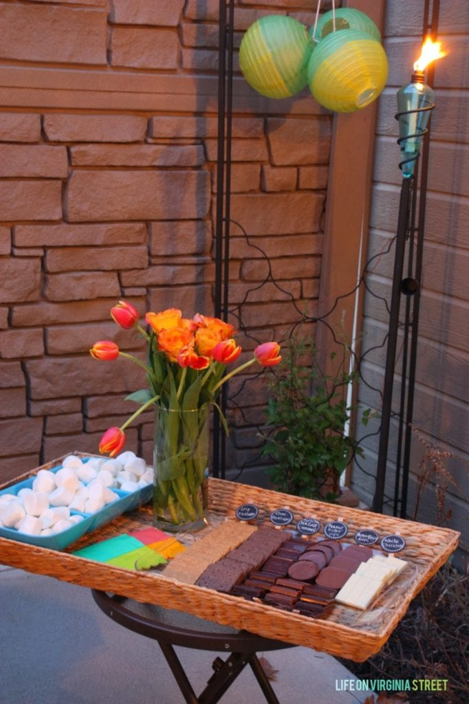 A tray filled with chocolate cookie wafers, flowers and marshmallows.