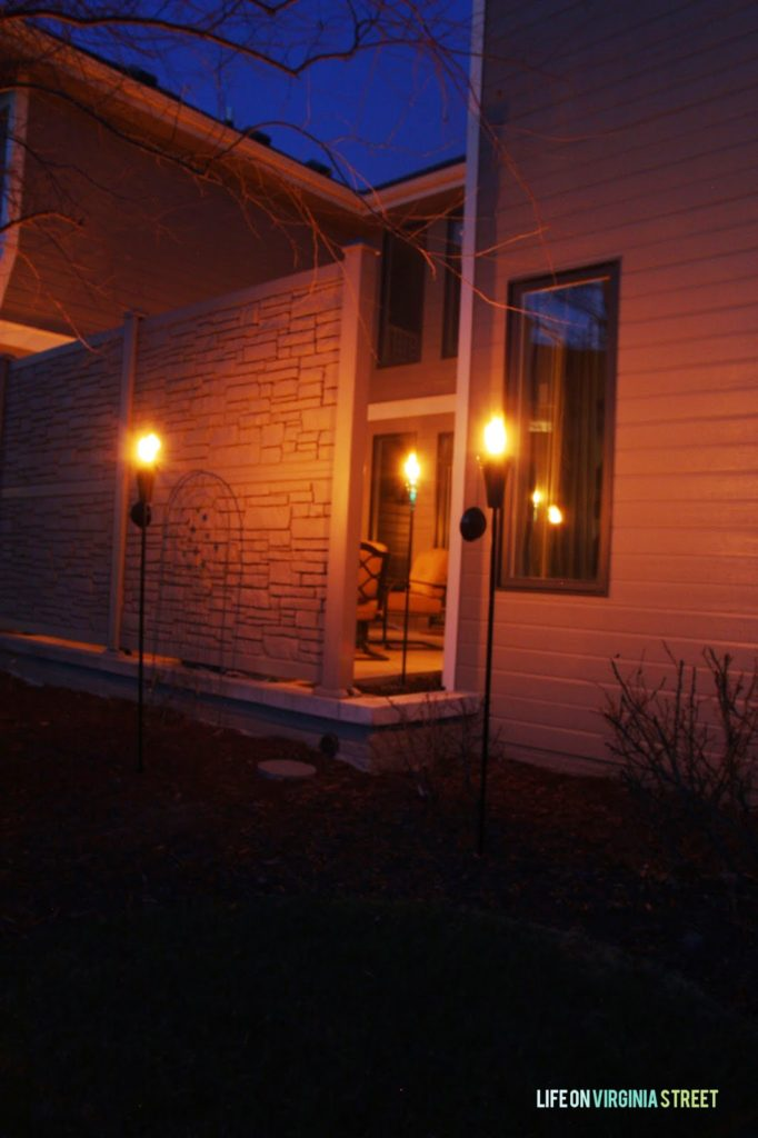 The warm glow of the outdoor lights illuminating the side of the house.