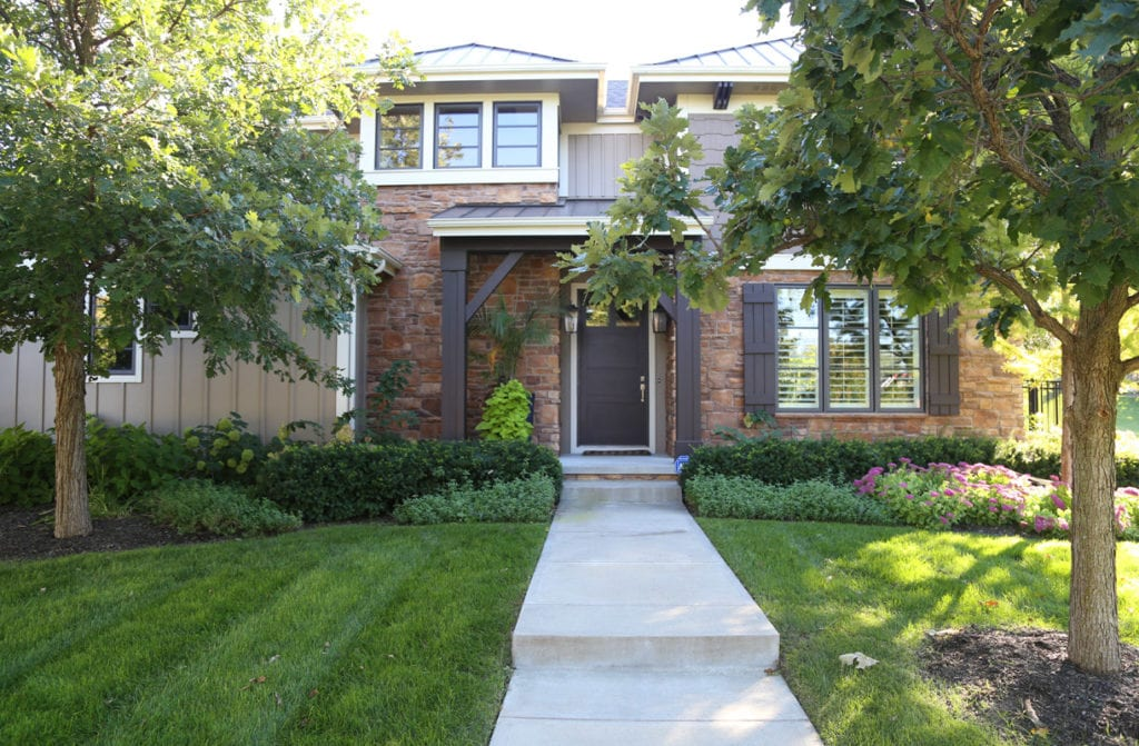 Modern craftsman style exterior house. Brown board and batten, rock facing, white trim, brown door, bronze window frames, metal roof.