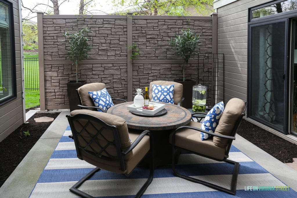 Gorgeous outdoor courtyard entertaining space. Love the blue and white striped rug, the blue and white trellis pillows, the oleander topiaries, the limes in the beverage dispenser, the white ceramic pineapple, and more!