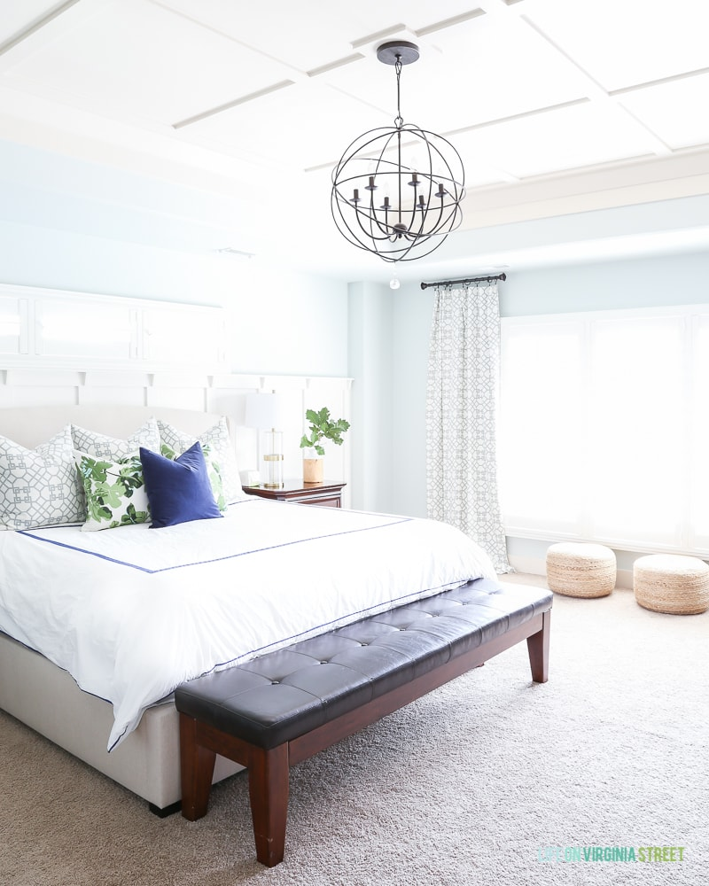 Master bedroom with Sherwin Williams Sea Salt walls, board and batten ceiling, white bedding, navy blue velvet pillow, fig leaf pillows, jute poufs and trellis curtains.