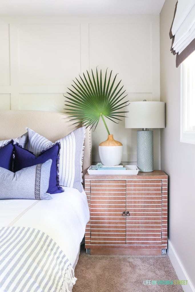 A coastal bedroom with white bedding, blue and white throw pillows, a linen bench, crystal semi flushmount chandelier, palmetto branch, white and wood vase, aqua lamp and ribbon-trimmed roman shades. Love that striped wood nightstand!