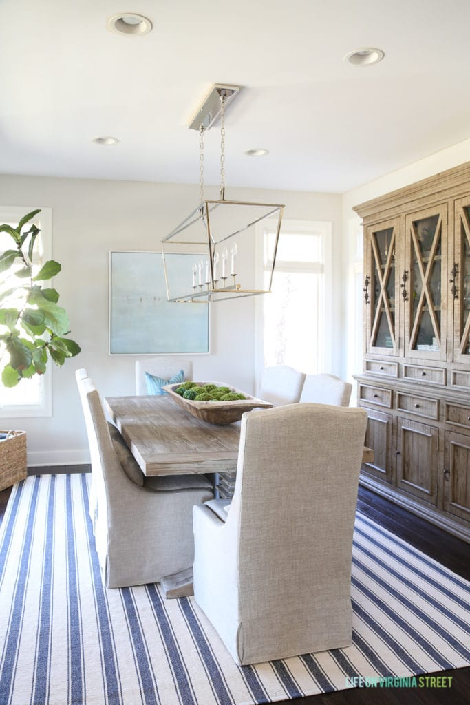 Coastal style dining room with navy blue and white striped rug, reclaimed wood hutch, driftwood color table, linen chairs, Darlana linear pendant light, fiddle leaf fig tree and beach art.