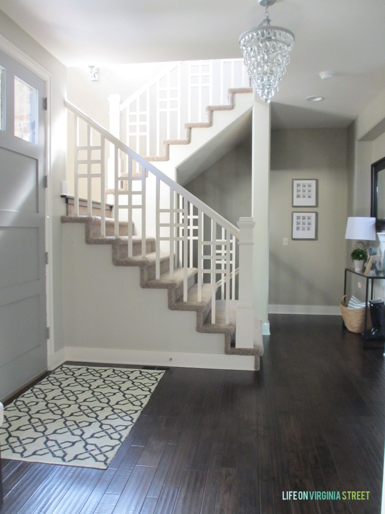 Dark wooden floor, and a winding staircase in the entryway.