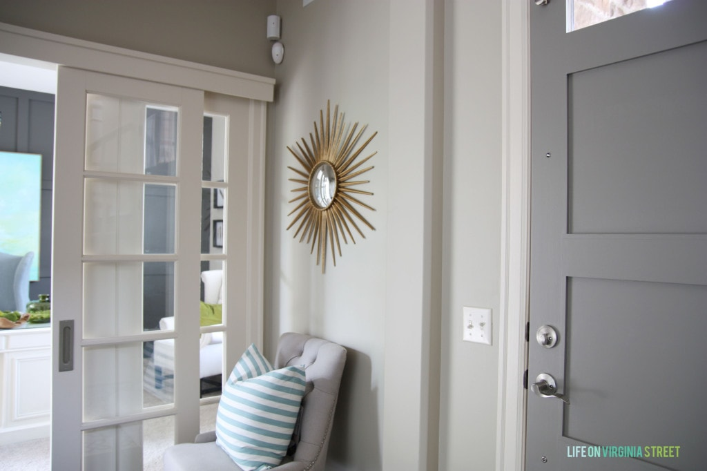 A gold sunburst mirror is on the wall above the chair in the hallway.