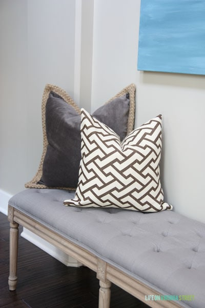 A wooden bench with a grey fabric cover and pillows on top of it.