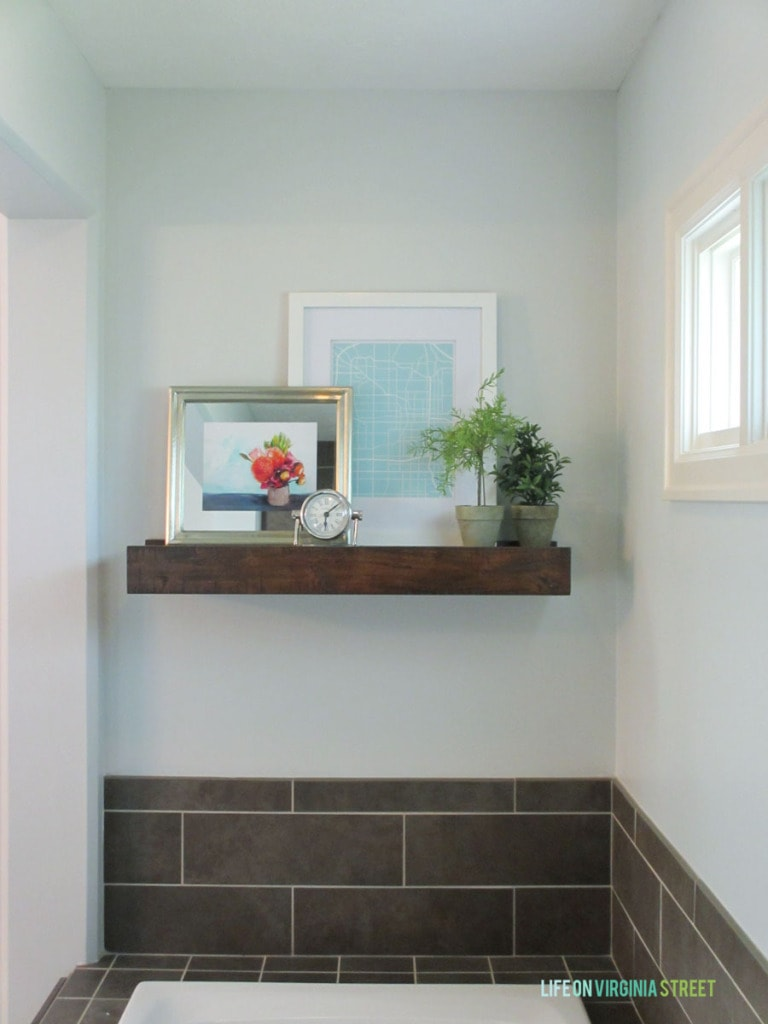 pottery barn rustic wood shelf in a master bathroom light gray walls and colorful artwork