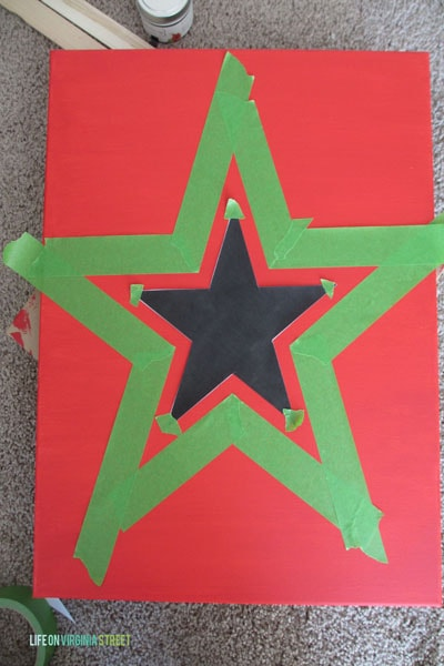 The star being outlined with green painters tape on red cardboard.