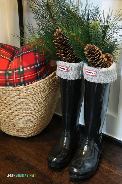 Cute Christmas entryway decor idea with boots filled with holiday greenery.