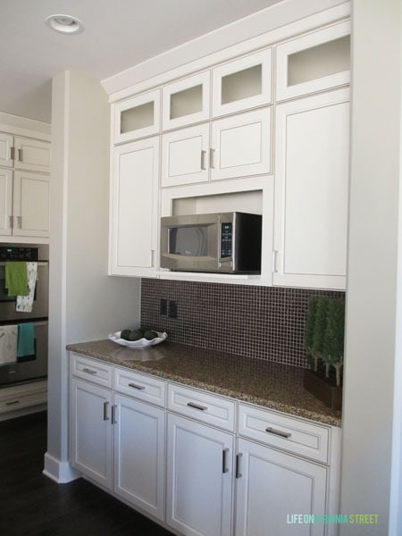 A white kitchen with dark counters and a built in microwave.