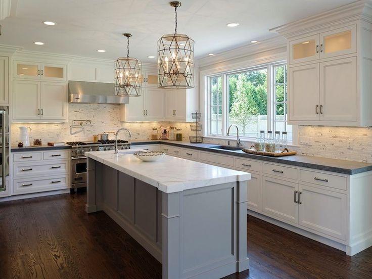 A white and gray kitchen with large chandelier lights above the island.