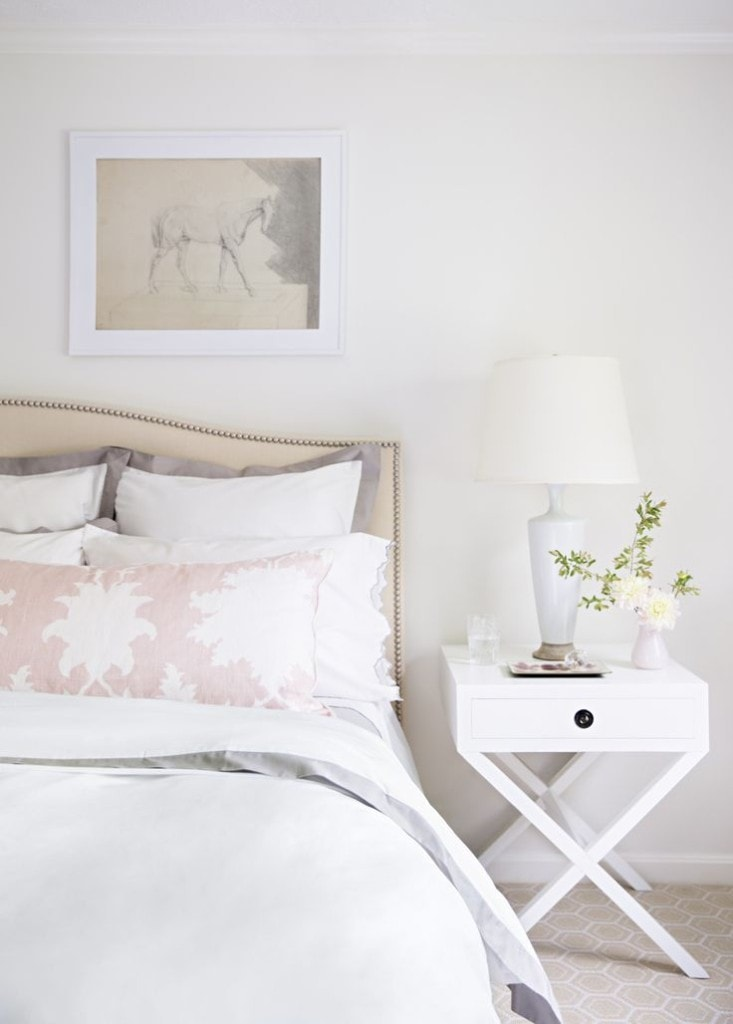 A white bedroom with a pink and white pillow and light pink vase on the nightstand.