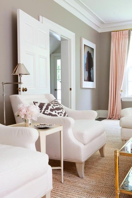 Neutral gray tones with blush pink curtains and flowers in the room.